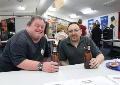 L:eigh Creighton and David Belcher smiling while drinking a beer