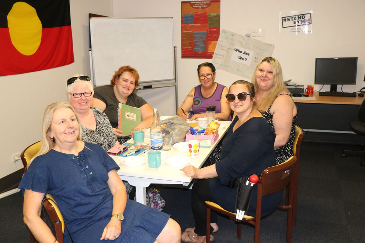 Women First Banner with group of happy women at a table, indigenous flag in background
