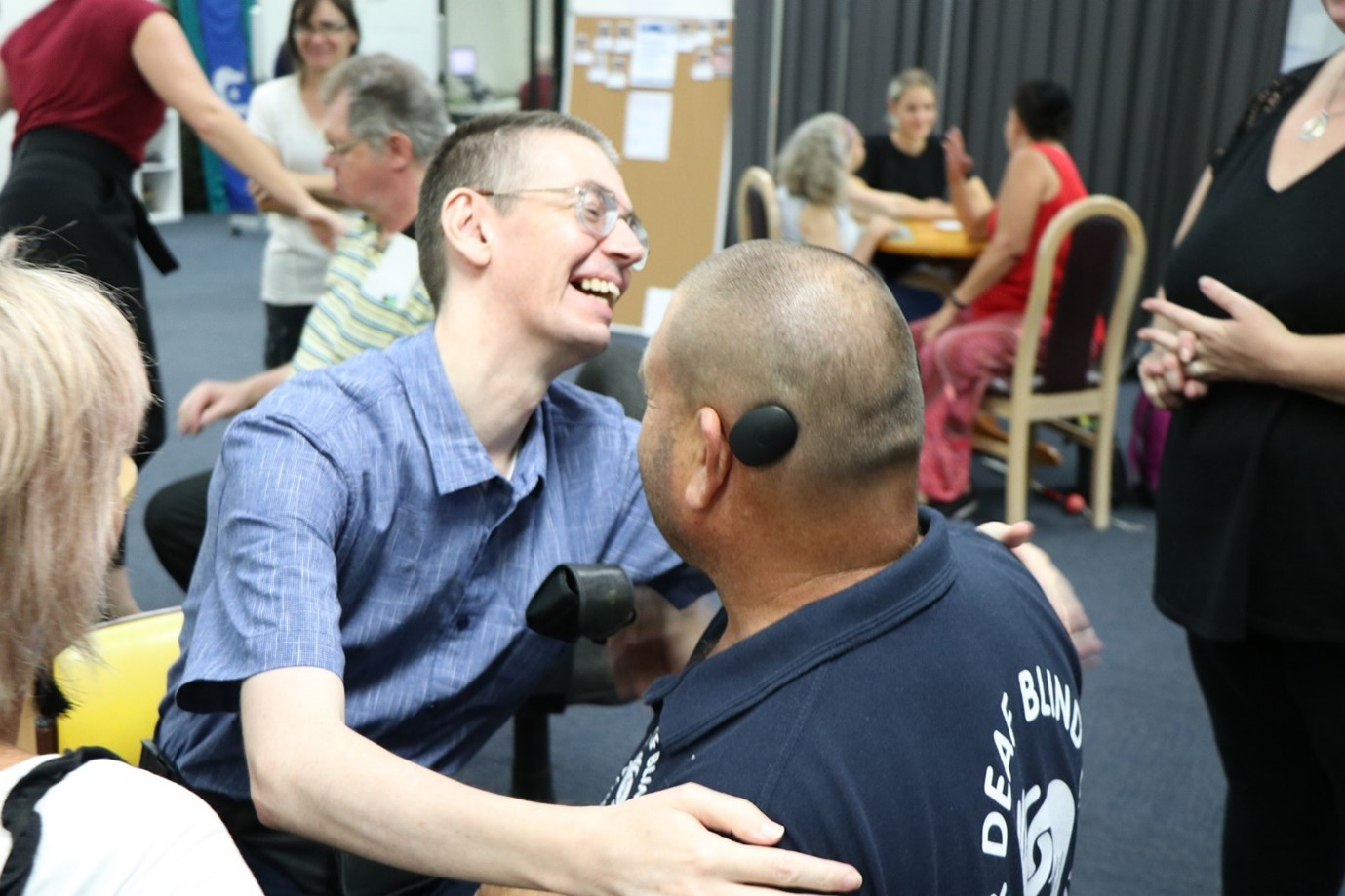 A photo of two Deafblind members smiling and hugging